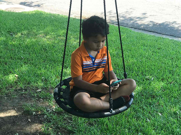 A young child sitting on a round swing, following christian kindergarten on his smartphone.