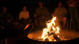 family-sitting-around-the-campfire-burni