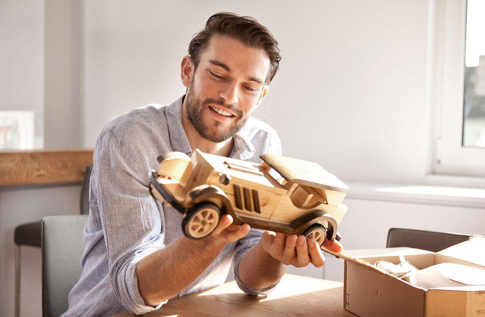 A man admiring a wooden car he crafted.
