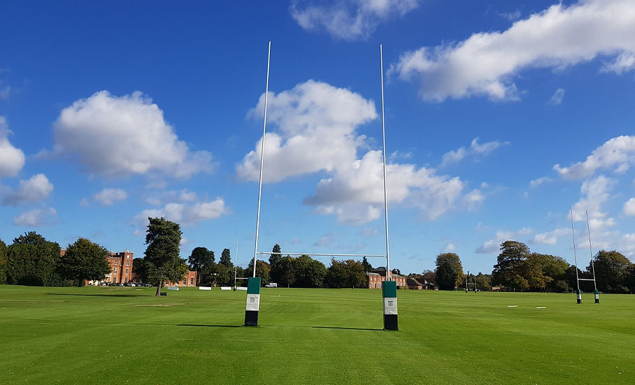 Set of lightweight hinged aluminium rugby posts from Harrod Sport on a school playing field.