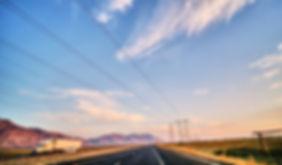 open highway in desert during sunset pow