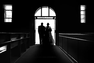 A silhouette of the bride and her father entering the church on her wedding day