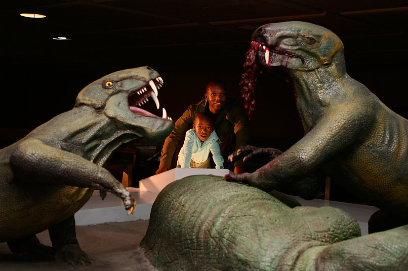 Father and son amazed at a dinosaur installation at the Iziko South African Natural History Museum