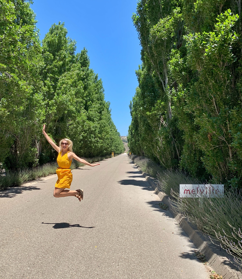 Wine blogger, Blonde Tasting, jumping for joy on the stunning entryway into the Melville Winery Estate in Lompoc, CA.