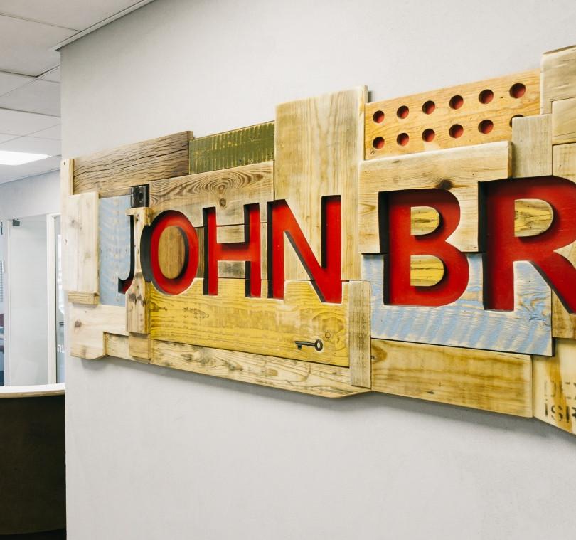שלט ודלפק כניסה למשרדי ג'ון ברייס' מעצים בשימוש חוזר ופח