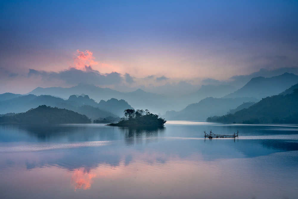 Cool sky-lit tones of dawn reflect dainty shades of periwinkle and pink off the surface of a calm lake.