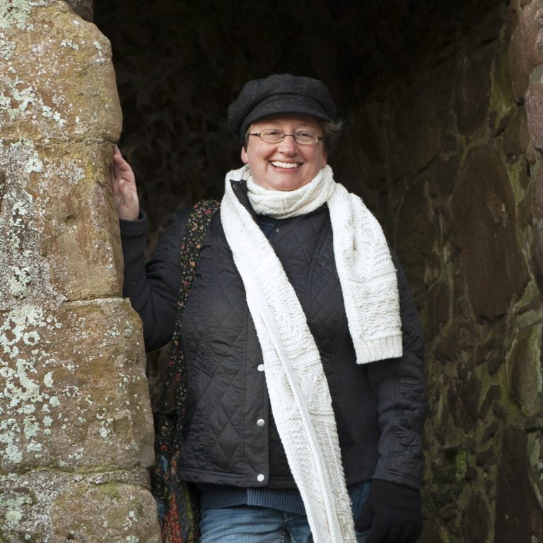 Headshot of Carmen Caine at  Dunnottar Castle in Scotland