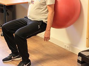 Squat met grote oefenbal, oefening voor het versterken van de beenspieren
