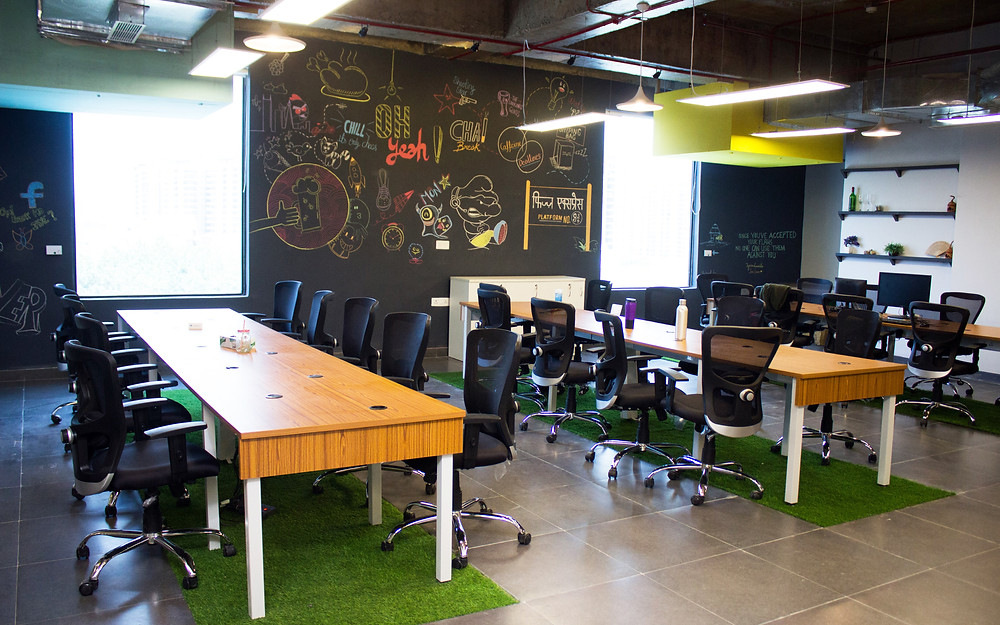 Customised workstation tables, with ergonomic chairs, grass mat underneath tables