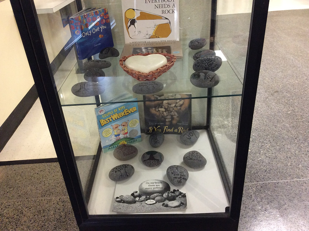 "A glass display showing the book ""Everybody needs a rock"""