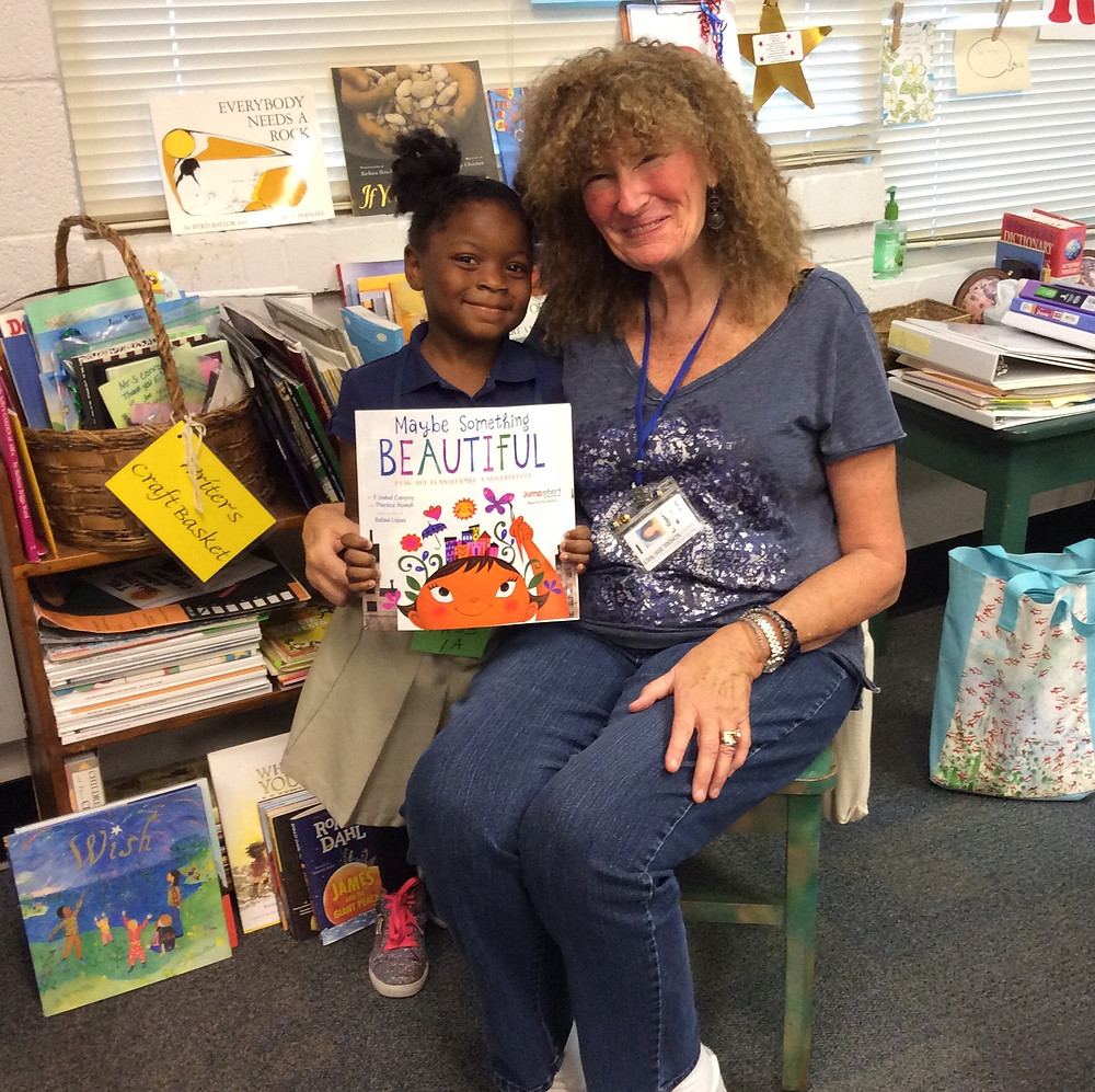 LaDene sitting down with a young student reading a book