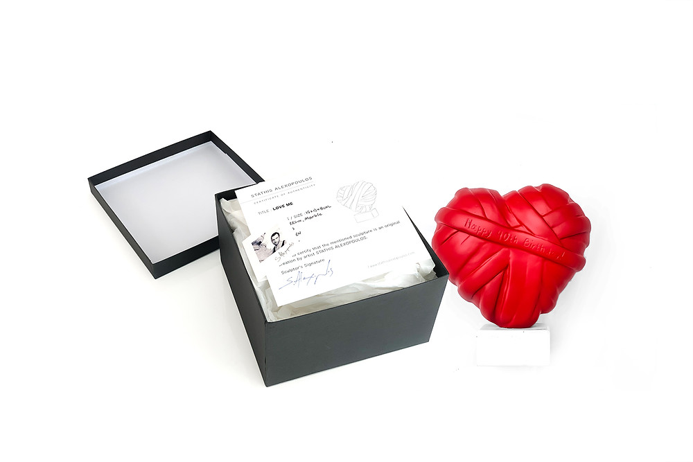 The red sculpture titled LOVE ME by stathis Alexopoulos, from heart series, with certificate of authenticity in gift box