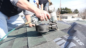 Roofing contractor using a nail gun to properly install an architectural shingle.
