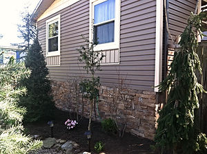 New siding, windows and manufactured stone wall on a ranch style house by WB 4 Construction Roofing Contractors.