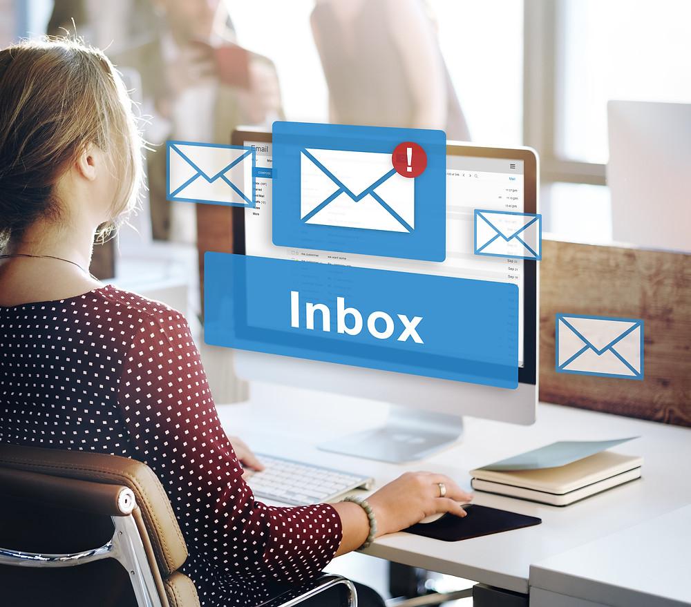 Frau an Apple-Computer liest E-Mails