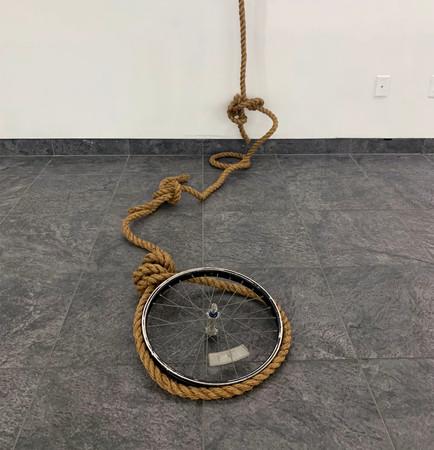 Steer [detail], 2020. Metal steer ornament, my dreads, artificial flowers, road, twine, bike wheel; Dimensions vary [Metal steer: 34 x 168 inches]