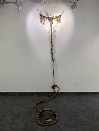 Steer, 2020. Metal steer ornament, my dreads, artificial flowers, road, twine, bike wheel; Dimensions vary [Metal steer: 34 x 168 inches]