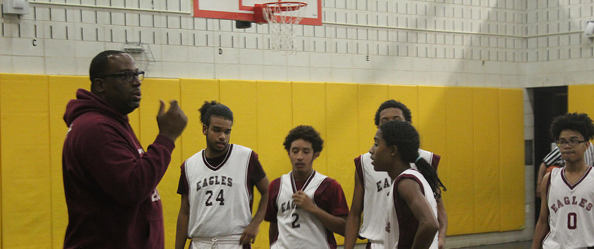 Coach K discussing strategy with New Heights JV Boys Basketball Team