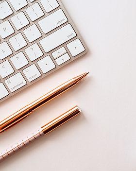 pen near black lined paper and eyeglasse