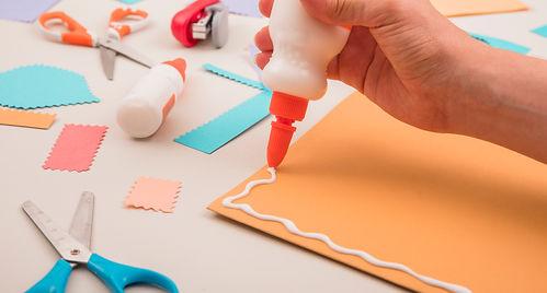 human-hand-applying-white-glue-orange-paper-with-scissor-stapler (1).jpg