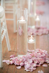 Floating candle vases with pink petals for wedding aisles