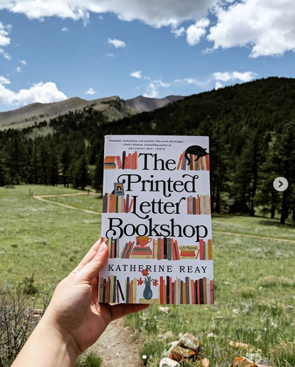 book in front of mountains and trees