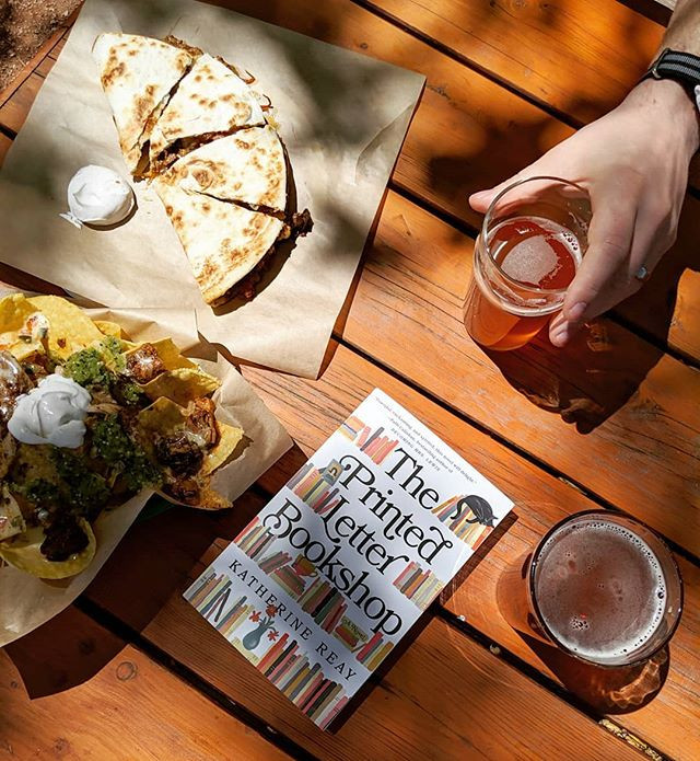 book next to nachos, quesadilla and beer on picnic table