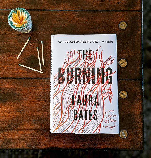 booksterjess The Burning book cover on a table next to matches