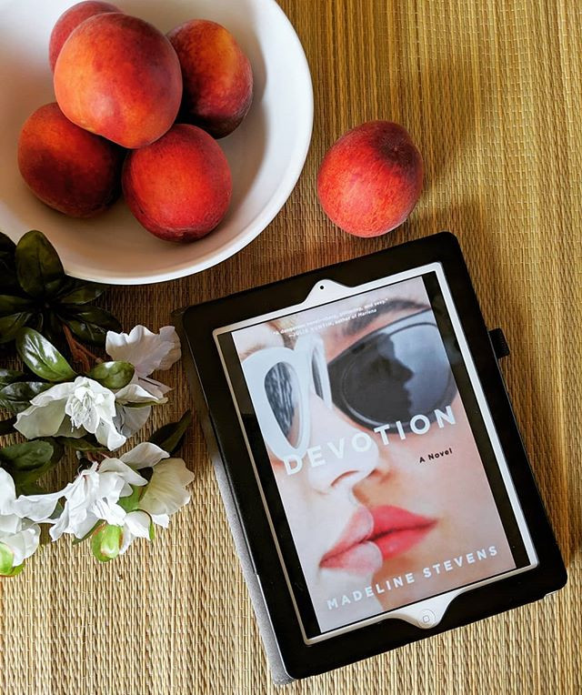 ebook next to flower bouquet and bowl of peaches