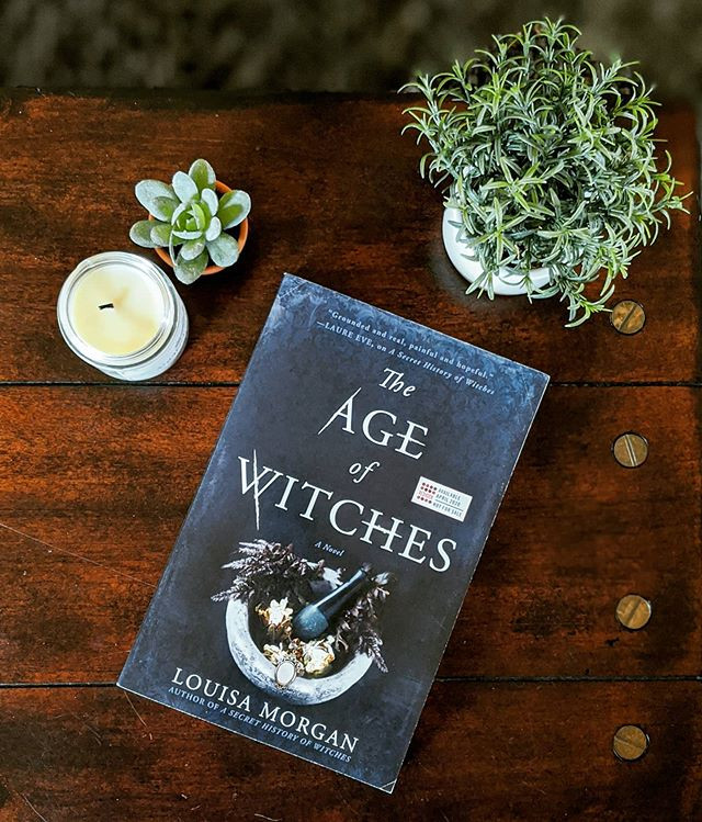 booksterjess The Age of Witches book laying on a table with plants and candle