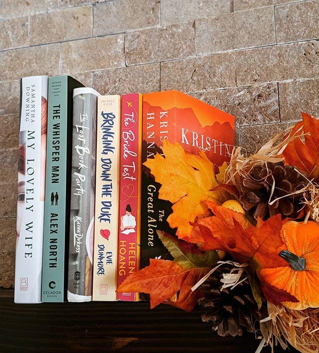 books on a bookshelf next to fall decor