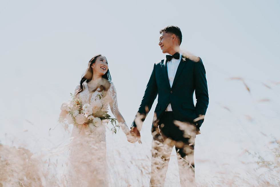 Bride and groom holding hands in a tall grass field, smiling, and enjoying their speical day.
