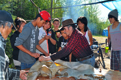 Cutting up moose hide for snowshoes