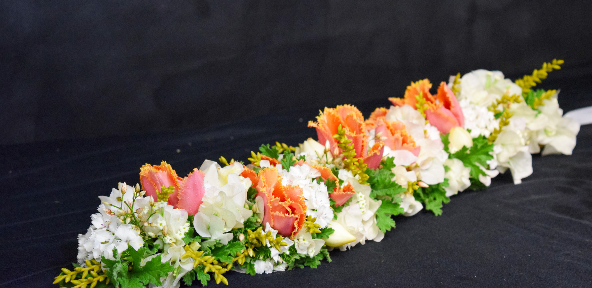 Mostly white with pops of orange and yellow lei po'o