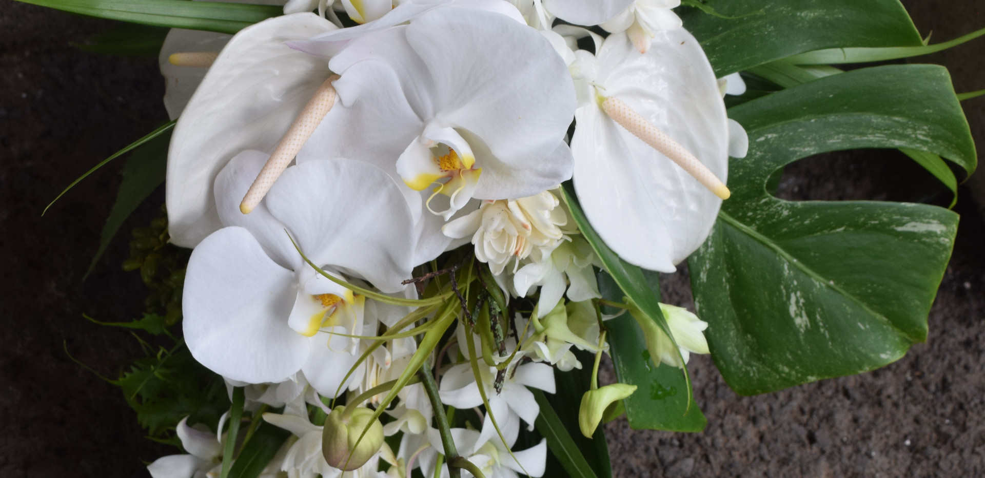 White cascade with organic tropical foliage accents