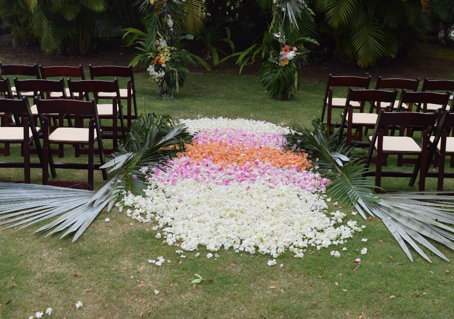 Palm leaves lining the aisle with thick ombre scatter