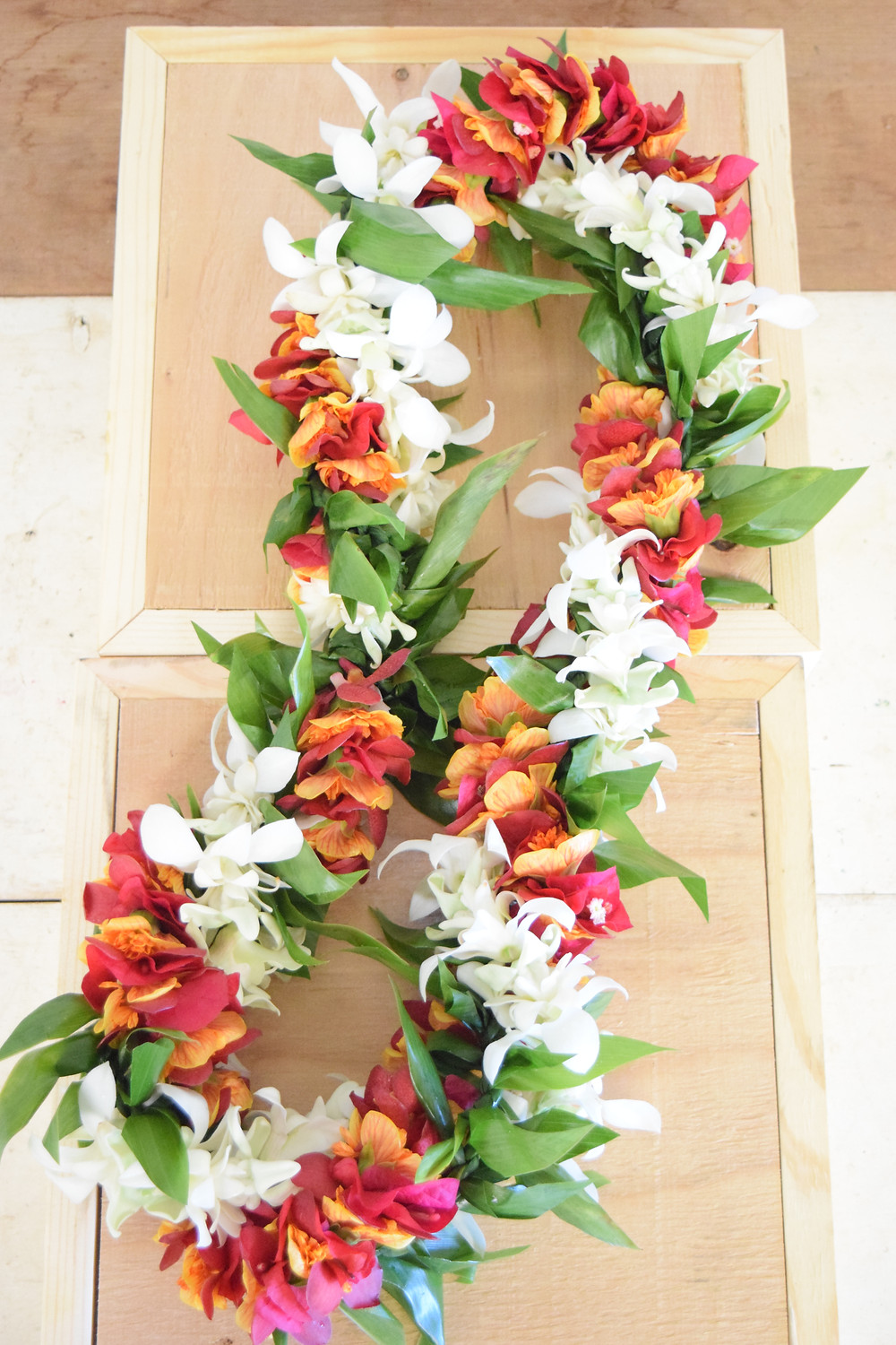 White crown flower, orchid and tuberose mix, maile-style ti leaf, and ilima-bougainvillea twist.