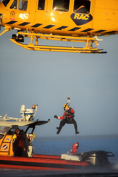 A Paramedic is winched aboard a rescue vessel from the Wespac helcopter..