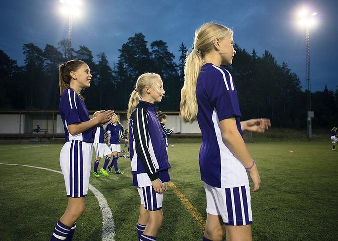 Girls Standing on Soccer Field
