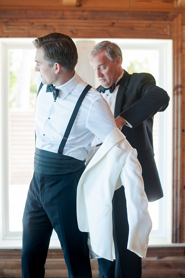 Father putting on his sons wedding coat