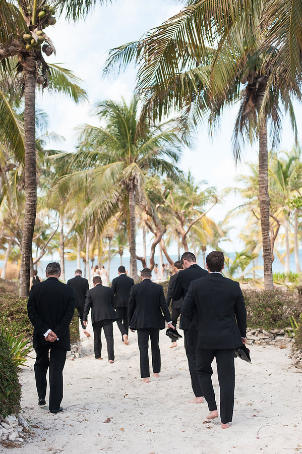 groomsmen walking towards the beach