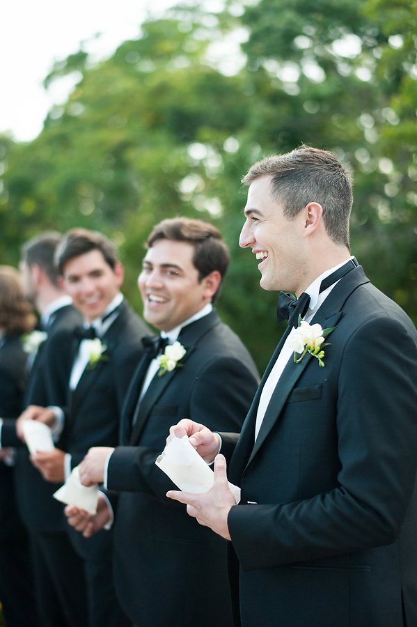 black and white candid photo of a groomsmen