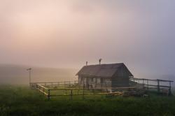 log cabin in the mist