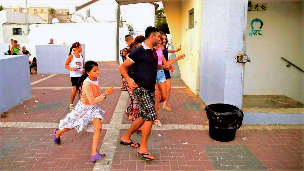 Illustration: Israelis Run For Shelter From Incoming Missiles by B'Tselem, Baz Ratner, Reuters [CC BY 4.0] via Wikimedia