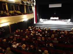 Photo of set on stage, and audience arriving for performance