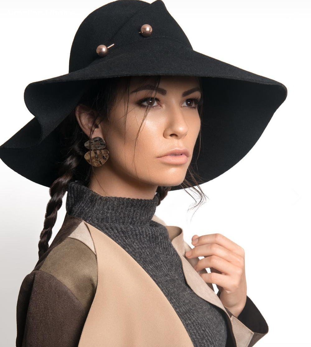 Head shot of Shaholly wearing a floppy hat, and long braid. She is wearing a grey turtle neck and a leather jacket.