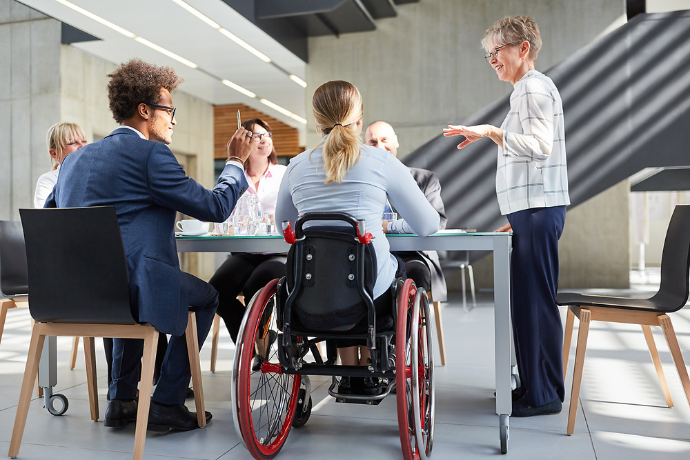 Image of coworkers sitting around a table. A women in a red wheelchair is at the forefront.