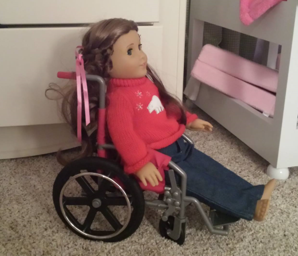 Image of American Girl Doll who is a wheelchair user in young girls room.