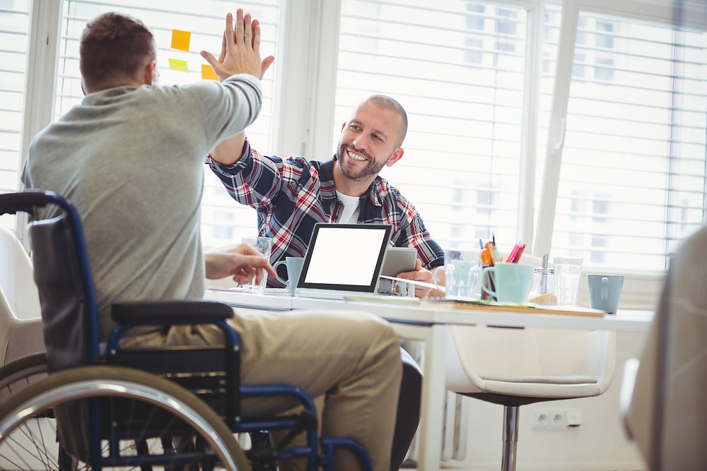 Wheelchair user gives a coworker a high-five
