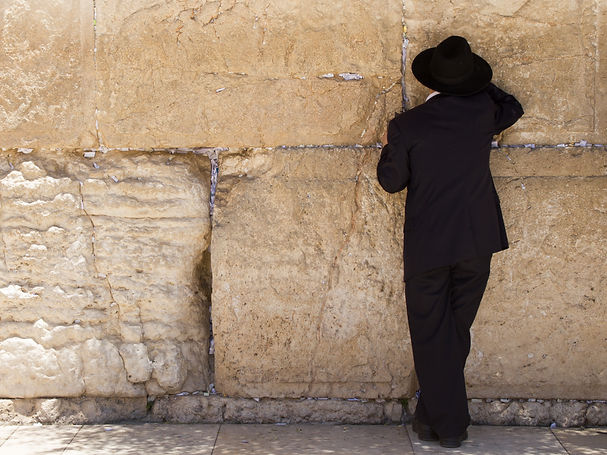 orthodox man with black clothes and hat praying at the Wailing Wall, Jerusalem.jpg